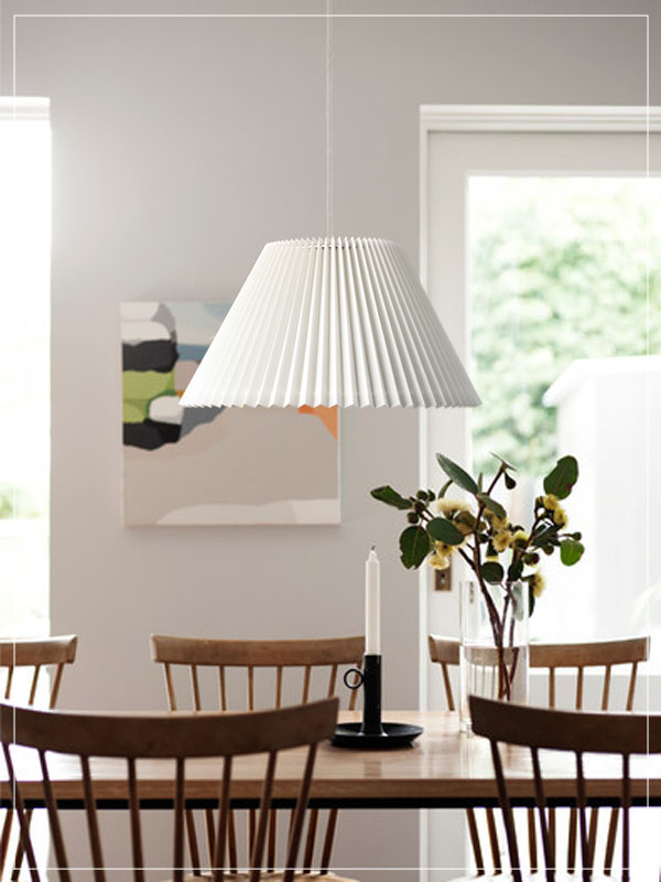 Pendant pleated lampshade in a dining room.