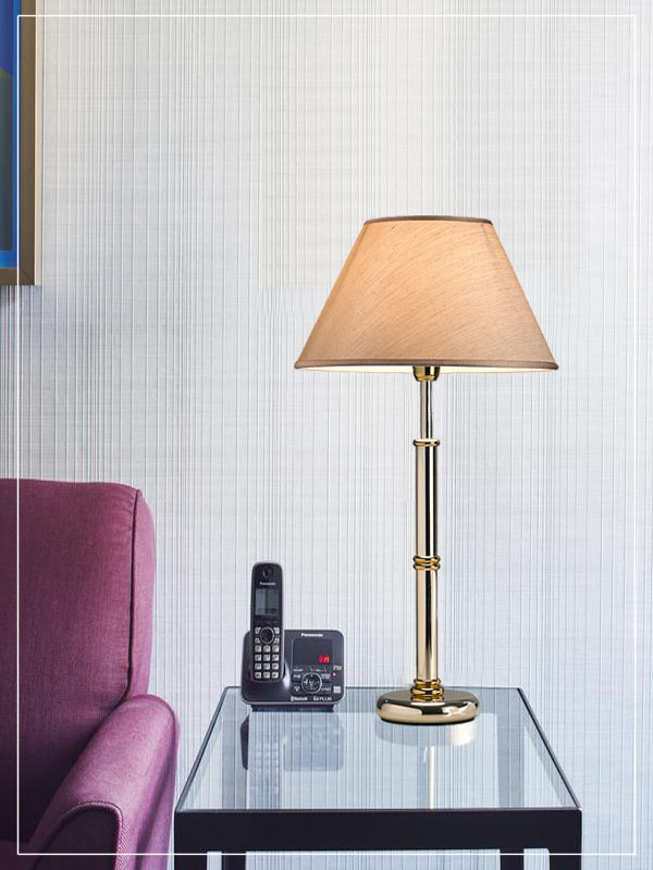 Table lampshade with metallized base in gold in a hotel room.